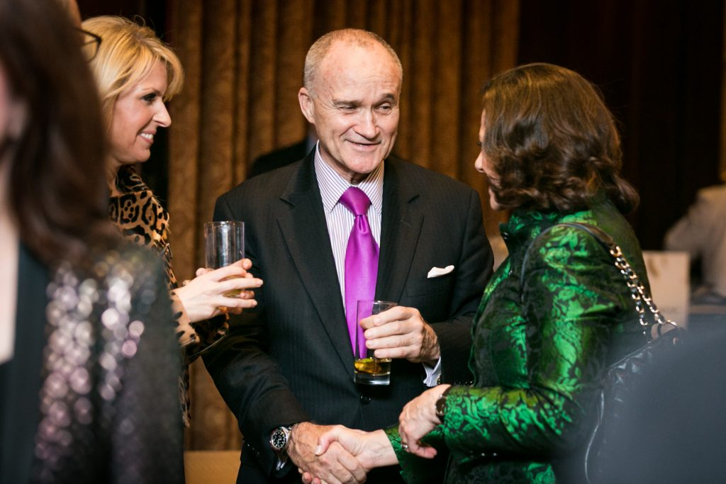 Business executives shaking hands at a cocktail party